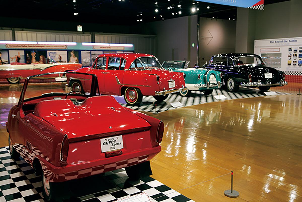 中段の写真の手前に置いてあるのは日本車で、愛知機械工業製の軽トラック、コニーグッピーを販売店がオープン・ボディに改装したモデル。