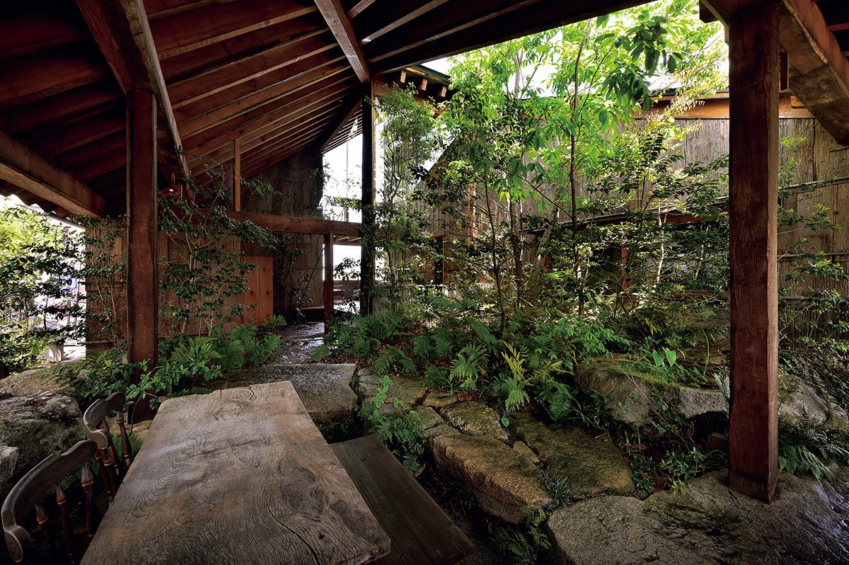 食事用のテーブルが置かれた、野趣溢れる前庭。その向こうに玄関が。